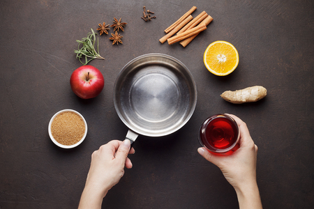 Hands cook mulled wine from ingredients on brown table. Stock Photo