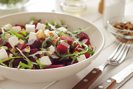 Vegetable salad with beetroot, arugula and feta for weight loss after holidays. Bowl of healthy diet food. Imagens