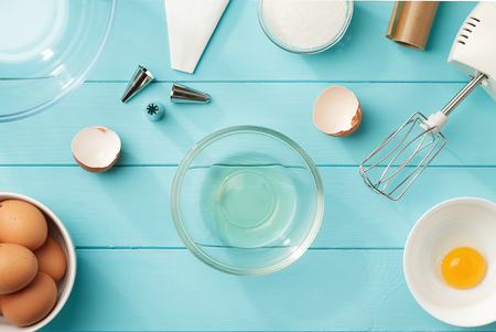 Culinary background with separated egg whites and yolks in the bowls on blue wooden table. Step by step recipe of meringue cookies top view. Foto de archivo