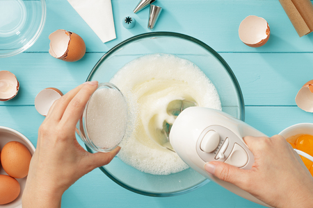 Female hands add a sugar to the bowl with whipping egg whites with mixer on blue wooden table. Step by step recipe of meringue cookies. Top view. Standard-Bild
