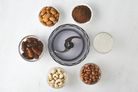 Ingredients for energy bites: nuts, dates, cocoa powder and coconut flakes with food processor on white wooden background. Step by step recipe of no bake gluten free brownie energy balls top view.
