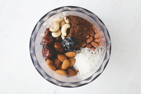 Ingredients for brownie energy bites in the food processor on white wooden table. Step by step recipe of healthy no bake energy balls top view.