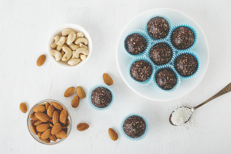 Healthy chocolate energy bites with nuts, dates, cocoa powder, coconut flakes on white table. Homemade gluten-free vegan healthy snacks top view. Stock Photo
