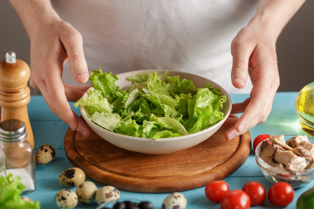 Hands take bowl with lettuce salad leaves from kitchen table with food.