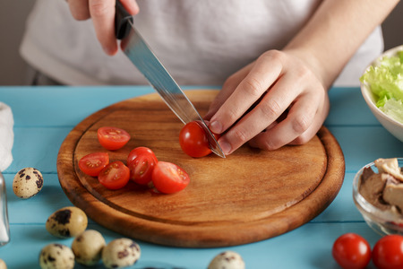 Man cuts cherry tomatoes on wooden cutting board in the kitchen.