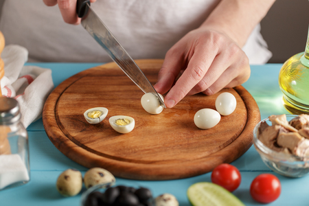 Chef cuts boiled quail egg on wooden cutting board on the blue kitchen table.