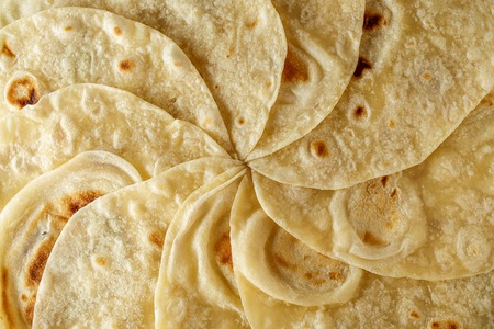Mexican tortilla wrap background or texture top view. Food flatbread pattern. Stock Photo