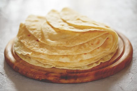 Homemade tortillas on the wooden cutting board.