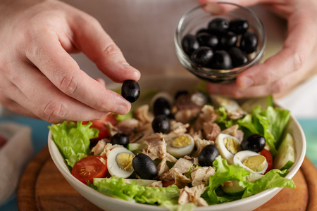 Hand put olive into the bowl with fresh vegetables and canned tuna.