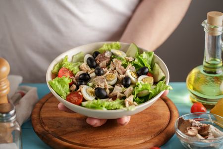 Chef serves bowl with tuna salad, cherry tomatoes and olives.