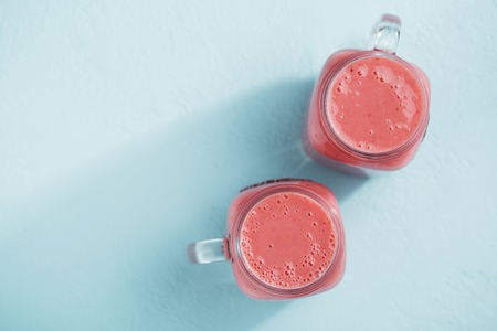 Two mason jars with strawberry smoothie on blue pastel background.