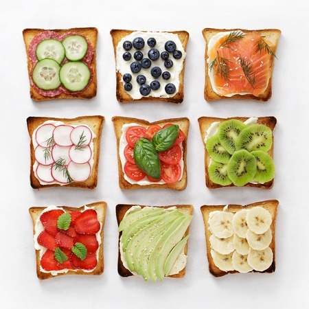 Set of various toasts with fruit, vegetable, fish and sausage and cheese on white baking paper.