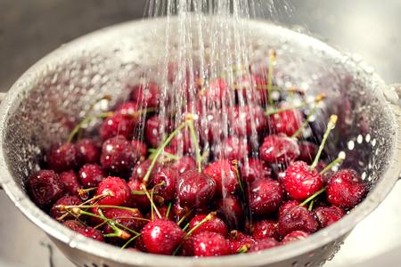 Washing sweet cherries in metal colander under water jet.