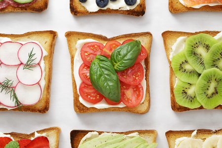 Various toasts with tomatoes, basil, cheese, kiwi, radish and other toppings on white parchment. Stock Photo
