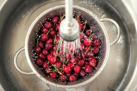 Sweet cherry washing in metal colander in the kitchen sink.