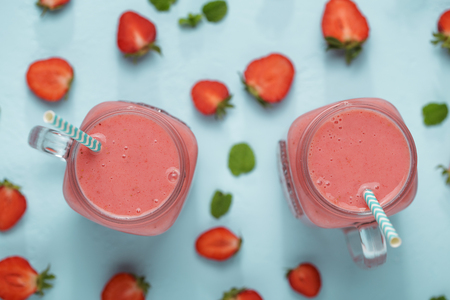 Mason jars with strawberry smoothie of milkshake on blue table with berries halfs.