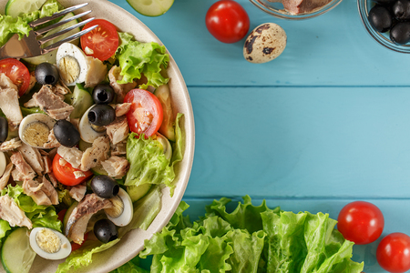 Tuna salad plate on blue wooden background. Top view with copy space.