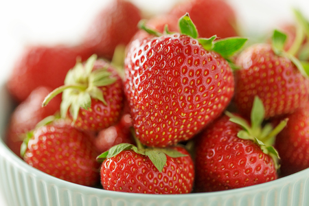 Fresh juicy strawberry in ceramic bowl close-up. Summer ripe berries for healthy diet. Stock Photo