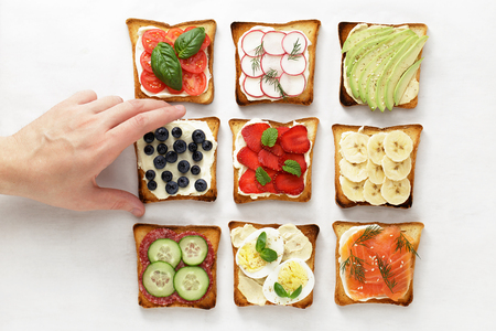 Male hand takes toast sandwich with soft cheese and blueberry. Various sandwiches with fruit, vegetables and meat.