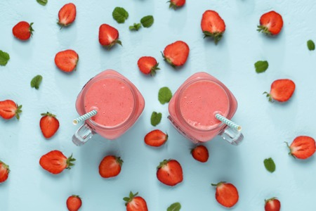 Two mason jars with strawberry on blue background top view. Stock Photo