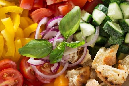 Food background with ingredients for mediterranean salad panzanella. Veggie texture of tomato bread greek salad top view. Banco de Imagens