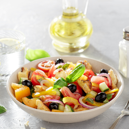 Fresh tomato salad panzanella with bread, olive, pepper and onion in the ceramic bowl on kitchen table with oil bottle. Italian healthy dish with fresh vegetables and ciabatta.