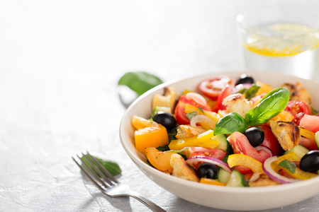 Mediterranean tomato salad panzanella with bread and fresh vegetables in the ceramic bowl. Summer healthy pomodoro salad with copy space. Stock Photo