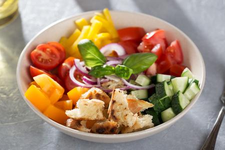 Ingredients for cooking mediterranean bread salad panzanella in ceramic bowl. Italian tomato, ciabatta, basil, onion, cucumber salad. Banco de Imagens