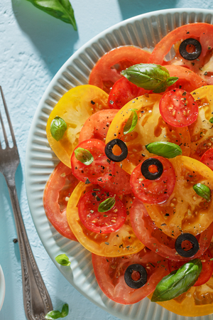 Homemade vegetable tomato carpaccio on blue plate with fork on blue background. Seasonal veggie salad for healthy diet top view.