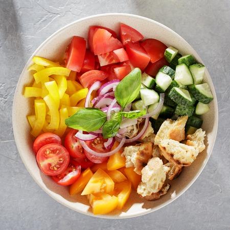 Ceramic bowl with fresh ingredients for mediterranean tomato bread salad panzanella. Top view, square crop. Banco de Imagens