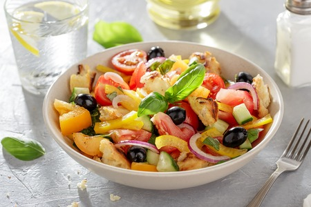 Panzanella bread salad in ceramic bowl on the table with fork, glass of water, salt and oil. Healthy summer vegetable dish for diet.