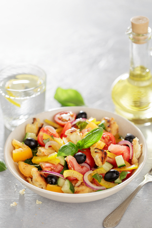 Fresh summer tomato ciabatta salad on the table with fork, lemon water and oil bottle, copy space. Stock Photo