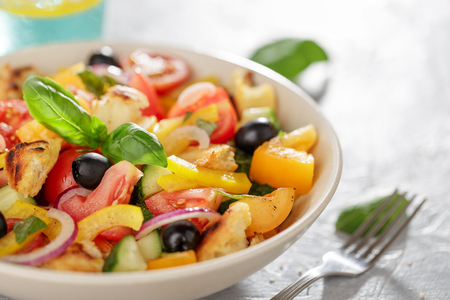 Panzanella salad with heirloom tomatoes and ciabatta in ceramic bowl on the kitchen table close-up. Stock Photo
