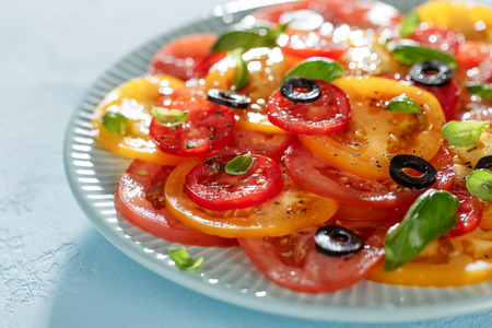 Fresh salad with red and yellow tomato slices, basil, olives and spices on blue plate. Homemade vegetarian carpaccio close-up. Stock Photo