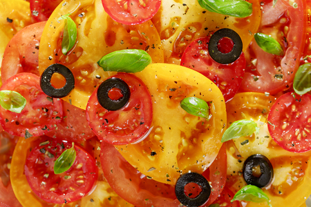 Vegetable background or texture of red and yellow tomato slices, olives and basil top view.