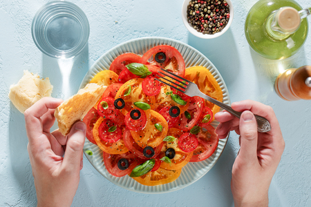 Male hands hold fork and piece of bread for and ready to eat tomato salad top view.