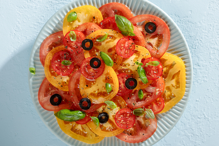 Blue plate with organic tomato salad with olives and basil on blue background top view. Stock Photo