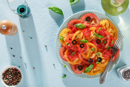 Fresh tomato salad with basil and olives on blue background. Top view with copy space.