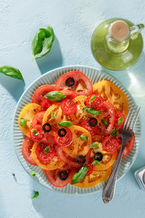 Red and yellow tomato slices with basil and olives on the plate on blue table, top view.