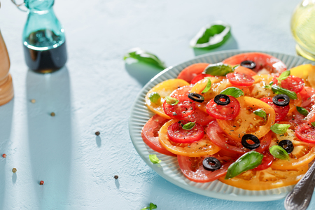 Homemade vegetarian tomato carpaccio salad in blue plate on blue background with copy space. Banco de Imagens - 105486509