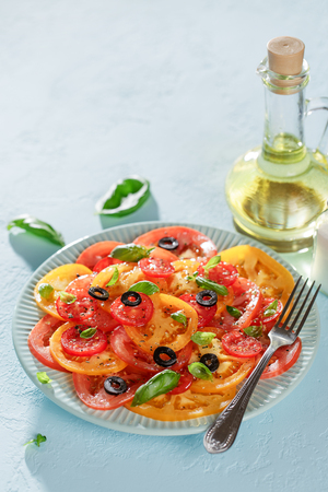 Veggie tomatoes summer salad with basil and olives on blue table with copy space. Stock Photo