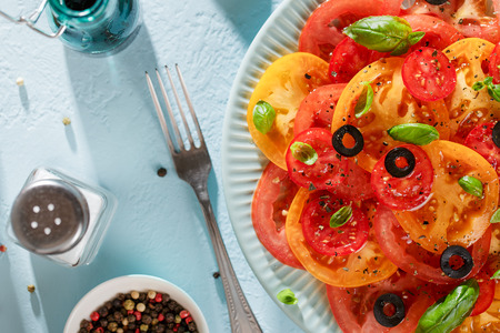 Seasonal tomato salad with basil, olives, spices and oil on blue table with fork and salt. Top view.