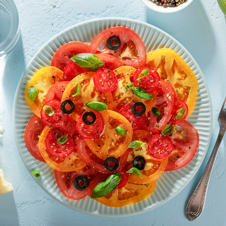Blue plate with homemade vegetarian tomato carpaccio on blue background. Fresh summer veggie salad for healthy diet. Top view, square crop.