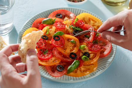 Male hands eat tomato salad with piece of bread with a fork. Personal point of view, pov. Banco de Imagens