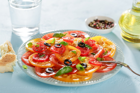 Blue plate with homemade tomato carpaccio on blue table with bread, water and oil.