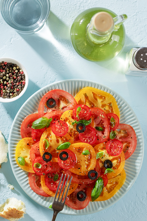 Fresh salad of red and yellow tomato slices on the plate on pastel blue background top view.
