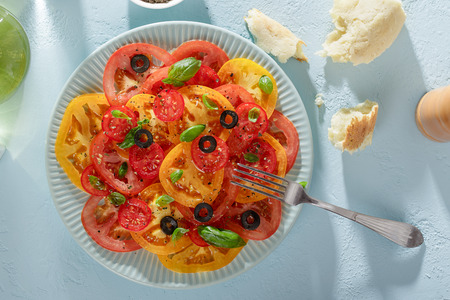 Healthy summer tomato salad and pieces of bread on blue table ready to eat top view. Stock Photo