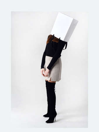 Portrait of teen girl with paper bag over head. Teenager cover head with bag with crossed arms.