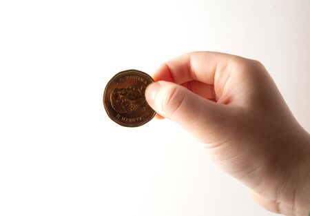 Child hand holding a coin on white background Stock Photo