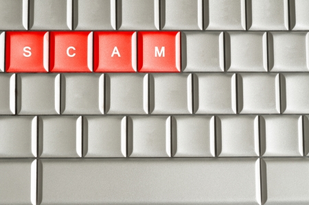 scamming: Scam word spelled on a metallic keyboard
